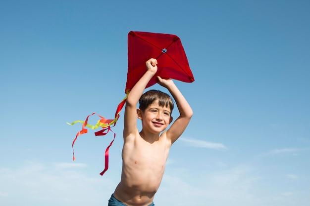 Garçon jouant avec un plan moyen de cerf-volant
