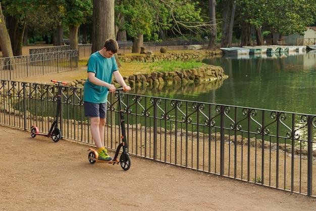 Garçon jouant avec son scooter dans le parc
