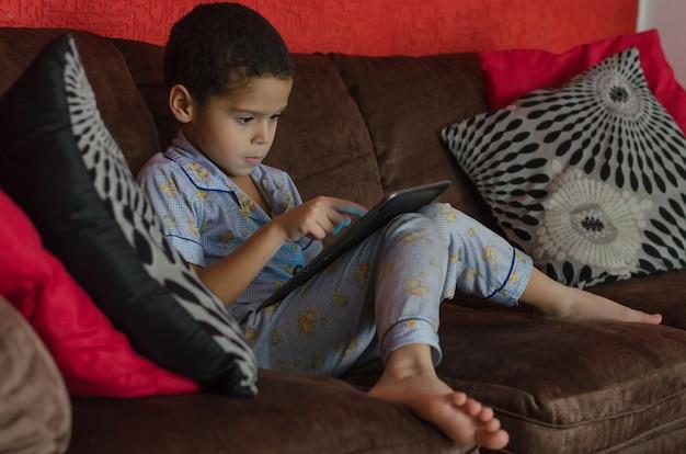 Garçon jouant avec tablette à l'intérieur, pendant la quarantaine