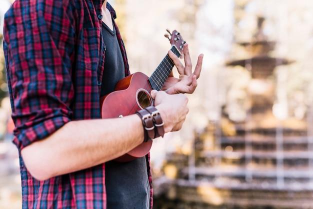 Garçon jouant de l'ukelele à côté d'une fontaine