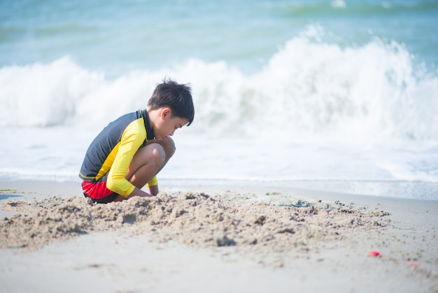 Garçon jouant des vagues et du sable sur la plage