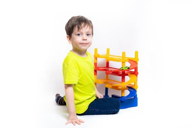 Garçon jouant avec des voitures dans le parking. jouet pour enfants. un garçon joue avec des jouets sur un mur blanc. parking lumineux pour voitures. enfance heureuse