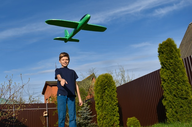 Un garçon joue avec un avion en plein air. avion jouet aérien. l'enfant lance un combattant. jeux en plein air.