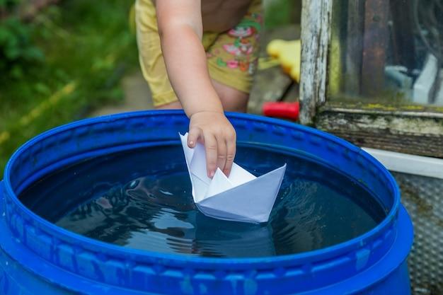 Un garçon joue avec un bateau en papier dans le tonneau d'eau dans le jardin