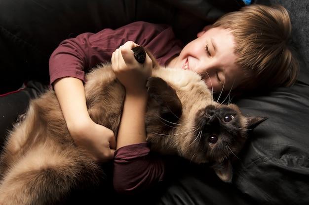 Un garçon joue avec un chat.