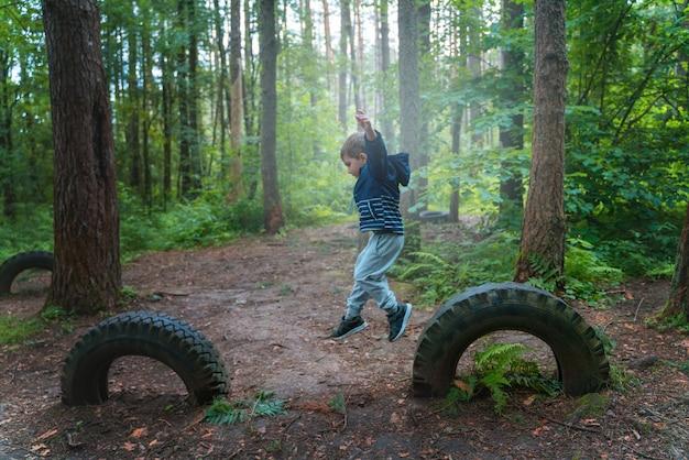 Garçon joue dans les bois et saute par-dessus les obstacles
