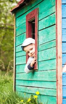 Le garçon joue dans la petite maison en bois de jouet extérieure