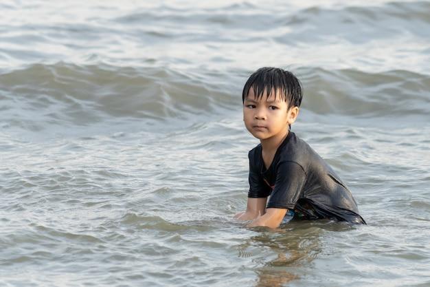 Garçon joue avec du sable et des vagues sur la plage