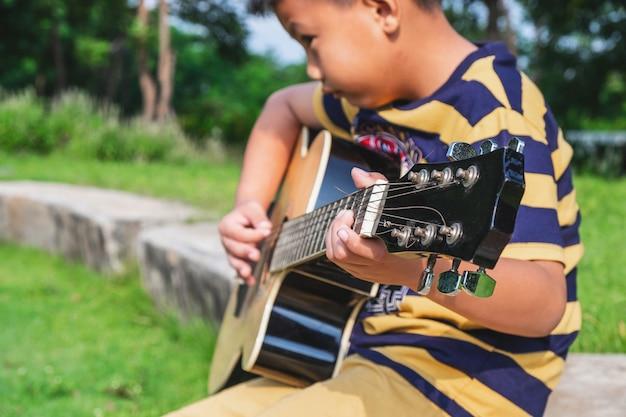 Le garçon joue de la guitare dans le jardin.