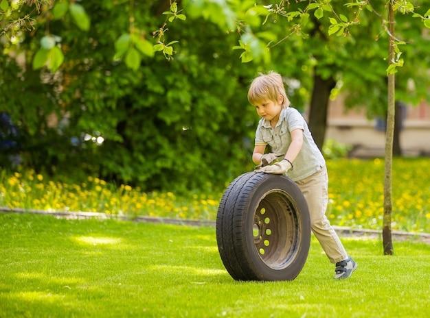 Un garçon joue avec la roue de la voiture dans le parc d'été