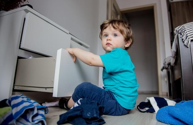 Garçon joue avec des vêtements de placard