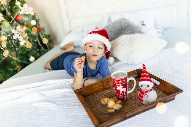 Garçon joyeux au lit mangeant des biscuits et buvant du cacao dans le chapeau du père noël arbre du nouvel an sur fond