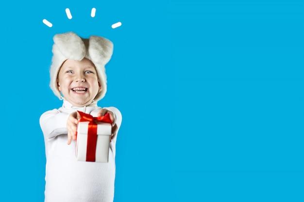 Un garçon joyeux dans un costume de lièvre blanc donne un cadeau avec un ruban rouge sur fond bleu