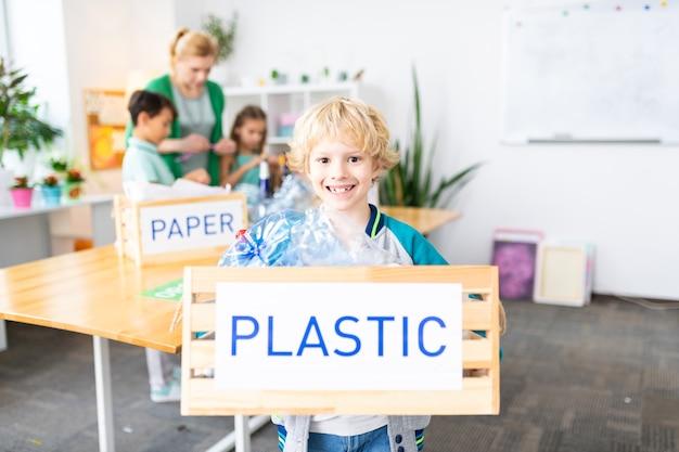 Garçon joyeux. joyeux garçon mignon aux cheveux blonds tenant une boîte avec du plastique après la leçon d'écologie
