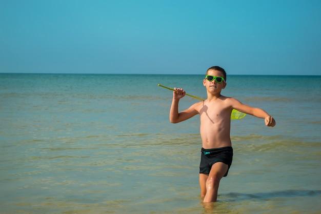Un garçon joyeux à lunettes de soleil se jette dans la mer avec un filet à papillons.