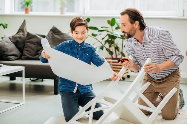 Garçon joyeux positif souriant et montrant à son père enthousiaste un dessin détaillé tout en aidant à assembler une nouvelle chaise sur le sol