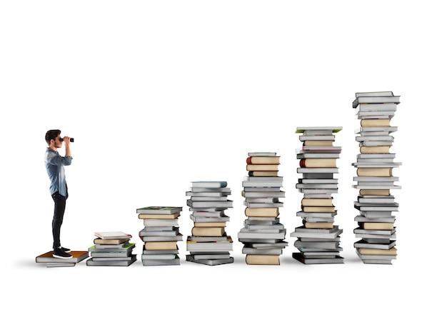 Garçon avec des jumelles sur une échelle de livres