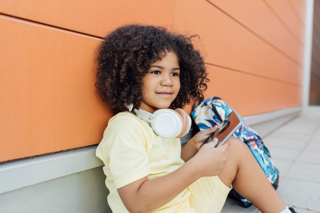 Garçon latin assis avec son sac à dos ailé tient son téléphone mineurs sourit au concept de l'école