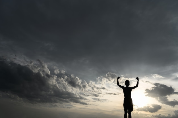 Le garçon leva la main dans le ciel pour demander de la pluie pendant le coucher du soleil.