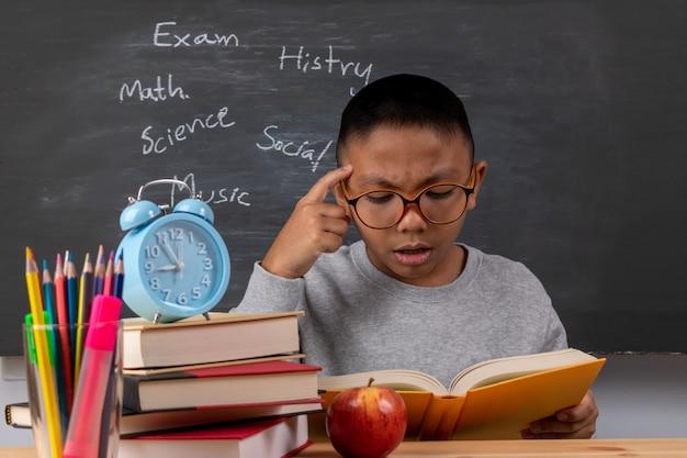 Un garçon en lisant des livres dans la salle de classe sur fond de tableau.