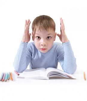 Le garçon avec le livre derrière une table