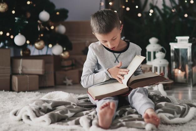 Garçon avec un livre magique sur le sol