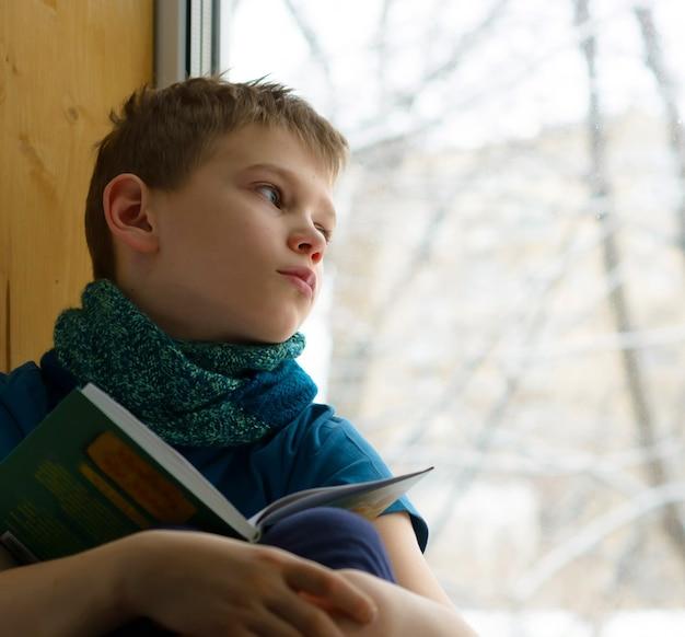 Garçon avec livre regardant par la fenêtre en hiver, à l'intérieur. un adolescent malade regarde par la fenêtre.