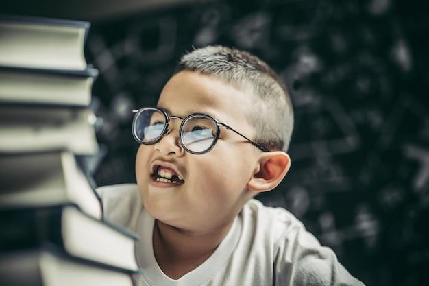 Un garçon avec des lunettes assis dans la salle de classe à compter les livres