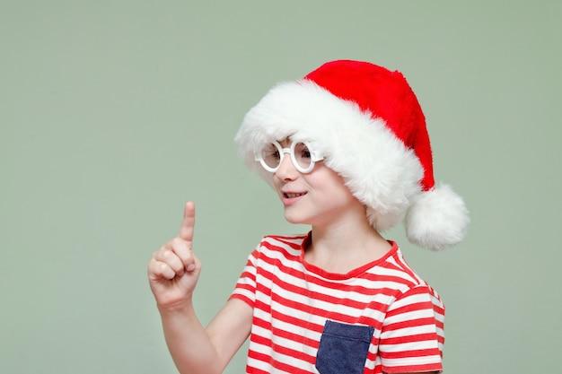 Un garçon avec des lunettes et un bonnet de noel menace avec son doigt. portrait