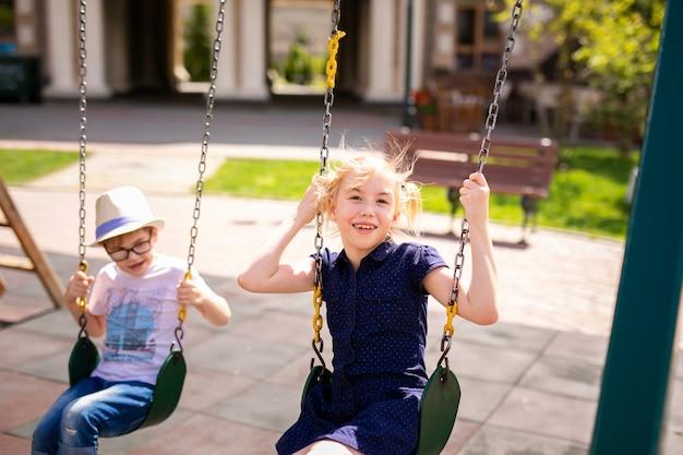 Garçon à lunettes et chapeau et fille blonde à la robe s'amuser sur une balançoire ensemble dans le magnifique jardin d'été.