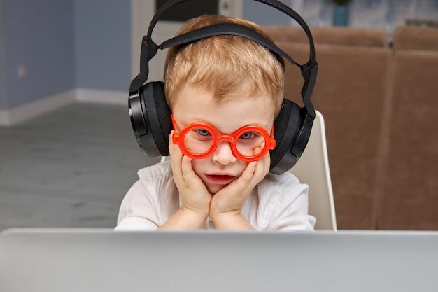 Un garçon avec des lunettes est choqué et surpris par ce qu'il a vu sur internet depuis un ordinateur portable