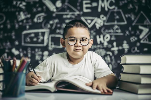 Un garçon avec des lunettes homme écrit dans la salle de classe