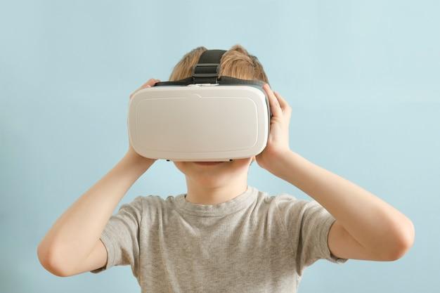 Garçon avec des lunettes de réalité virtuelle. fond bleu