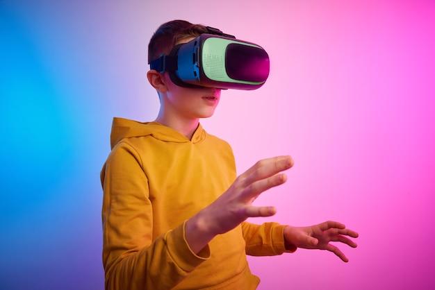 Garçon avec des lunettes de réalité virtuelle sur le fond coloré. technologie du futur, concept vr