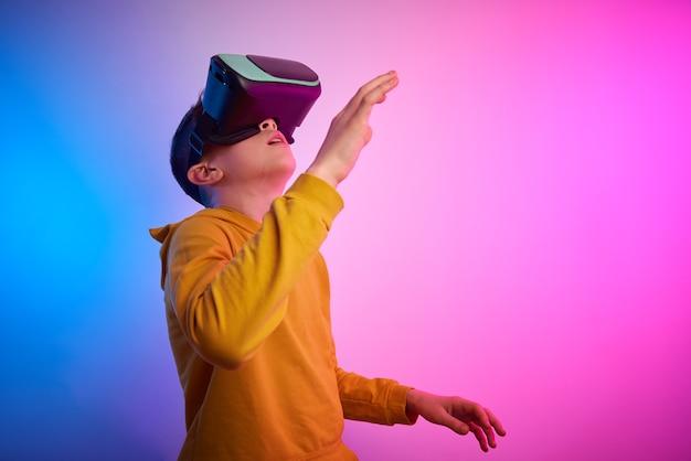 Garçon avec des lunettes de réalité virtuelle sur le fond coloré. technologie future, concept vr