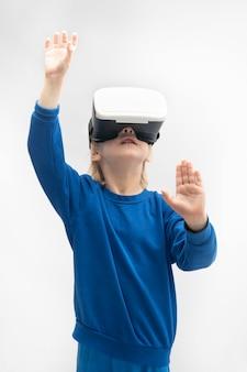 Garçon à lunettes de réalité virtuelle isolé sur fond blanc. jeux de réalité virtuelle. cadre vertical.