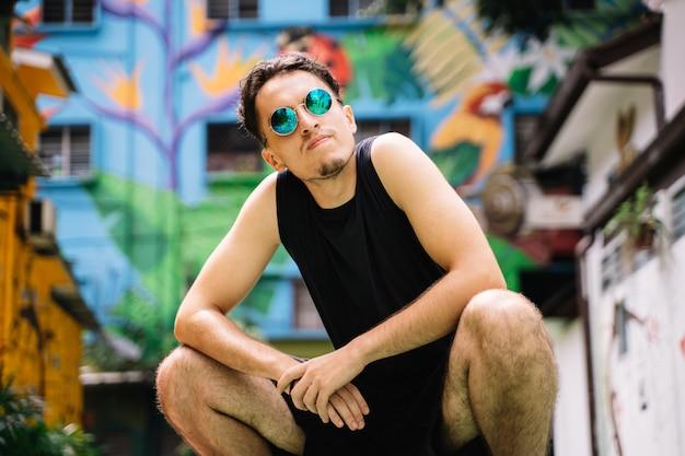 Garçon avec des lunettes de soleil réfléchissantes accroupi au milieu d'une rue aux façades colorées