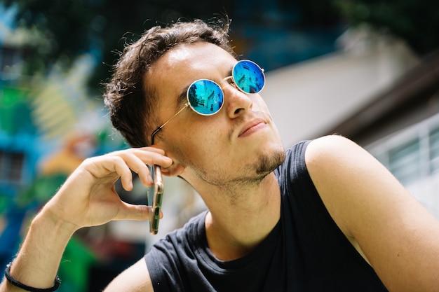 Garçon avec des lunettes de soleil réfléchissantes parler à son téléphone portable au milieu d'une rue aux façades colorées