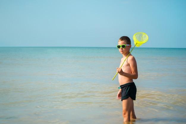 Garçon à lunettes de soleil se tient dans la mer avec un filet à papillons.