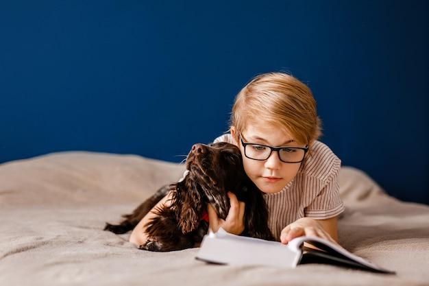 Garçon avec des lunettes et avec son chien est allongé sur le lit en lisant un gros livre.