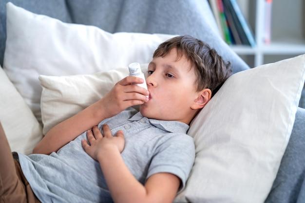 Garçon malade fatigué de la toux thoracique tenant l'inhalateur, souffrant d'asthme à l'aide de l'inhalateur.