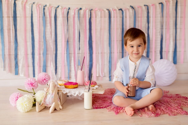 Un garçon mange des beignets et boit du lait d'une paille