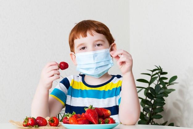 Garçon mange des fraises avec masque