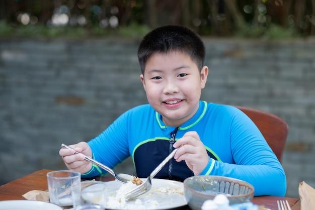Garçon mangeant de la nourriture, temps heureux
