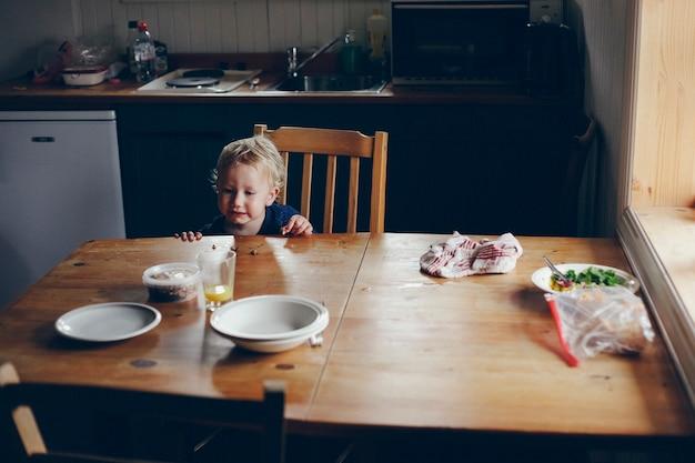 Garçon mangeant sur une table en bois vintage