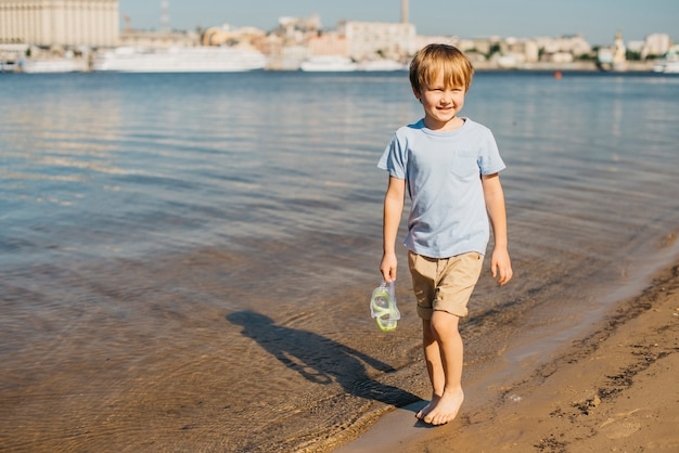 Garçon marchant le long du rivage