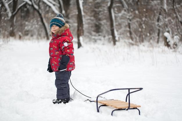 Garçon marchant avec des traîneaux dans la forêt d'hiver couverte de neige