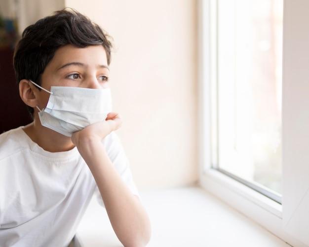 Garçon avec masque à la fenêtre