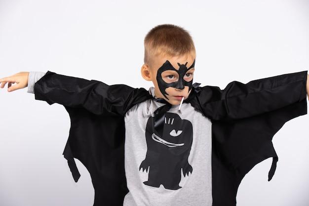 Un garçon de la maternelle en costume de chauve-souris lors d'une fête d'halloween avec une dame. bonbons et vacances pour les enfants.