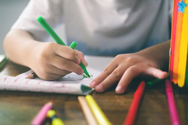 Garçon de maternelle dessinant et apprenant à la maison. éducation, concept d'apprentissage à distance.